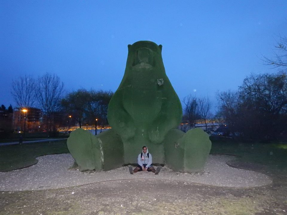 A huge bear 4 times a mans average height sits in the park made from astro-turf. In between his legs sits a man in a grey hoodie.