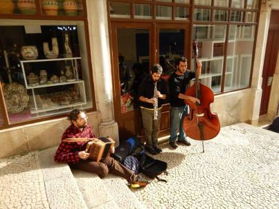three musicians play on the streets of Portugal. One man in a checkered shirt plays the accordian on the floor. The middle man plays a brass instrument and the final man is playing bass.