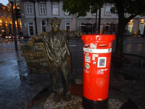 A bronze statue of a man is delivering post into a red post box