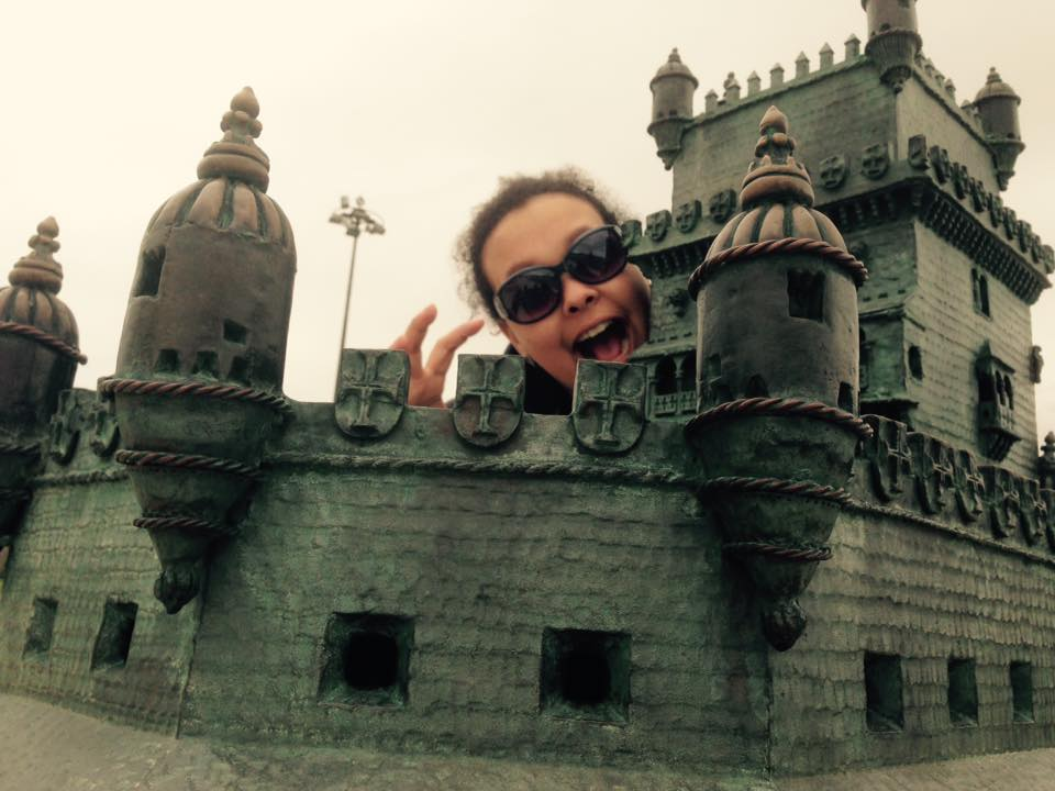 person pretending to eat the mini model of Belem tower in Portugal