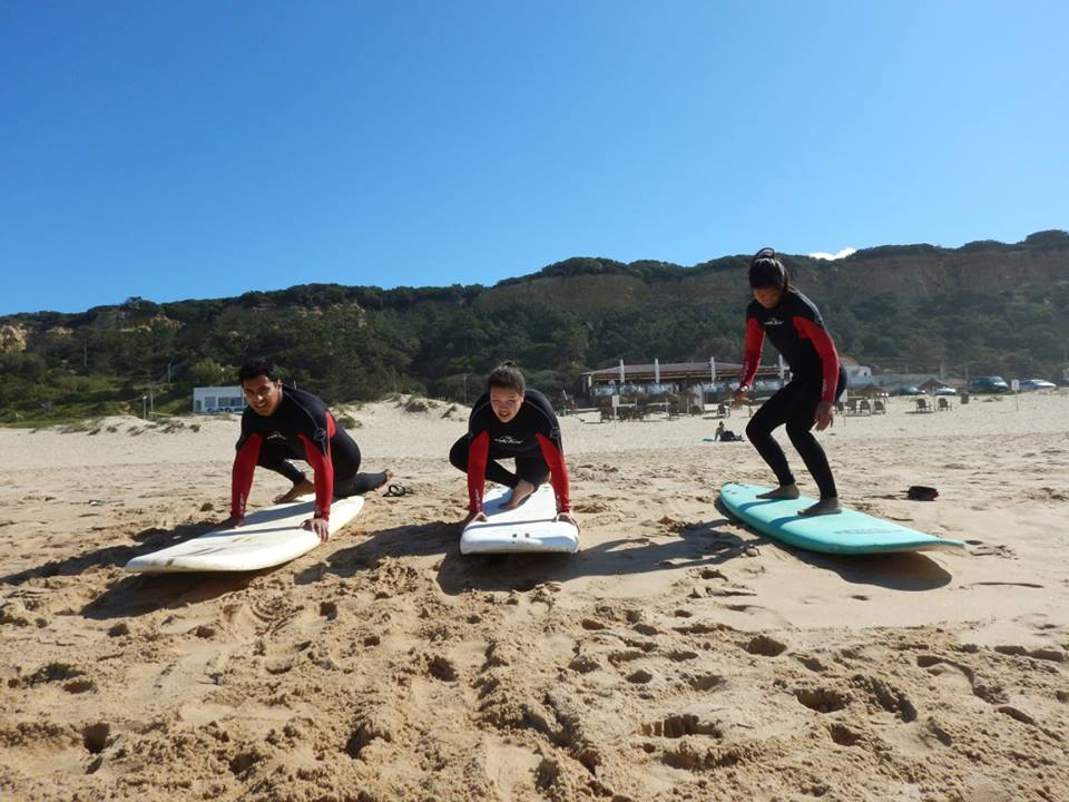 one man and two women are on the sand on their surfboarsd. the first man and woman are in a crouching pose facing the camera and gripping the board ready to stand up. The other woman is stood up balancing with her face looking towards her feet.