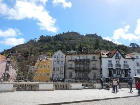 The big hill at Sintra. You can just about see the small forttress at the top. in the foreground you can see some of the buildings in Sintra. One is bright yellow and the others are grey and white