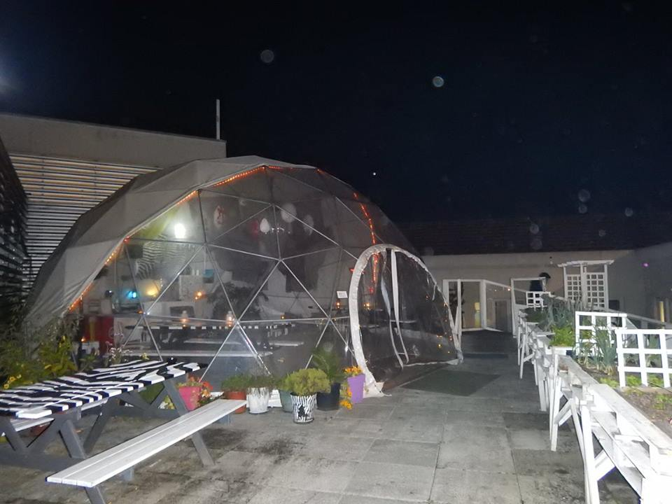 a plastic dome tent with a bar and seating inside in Lisbon Portugal on a roof top. It is night time and raining