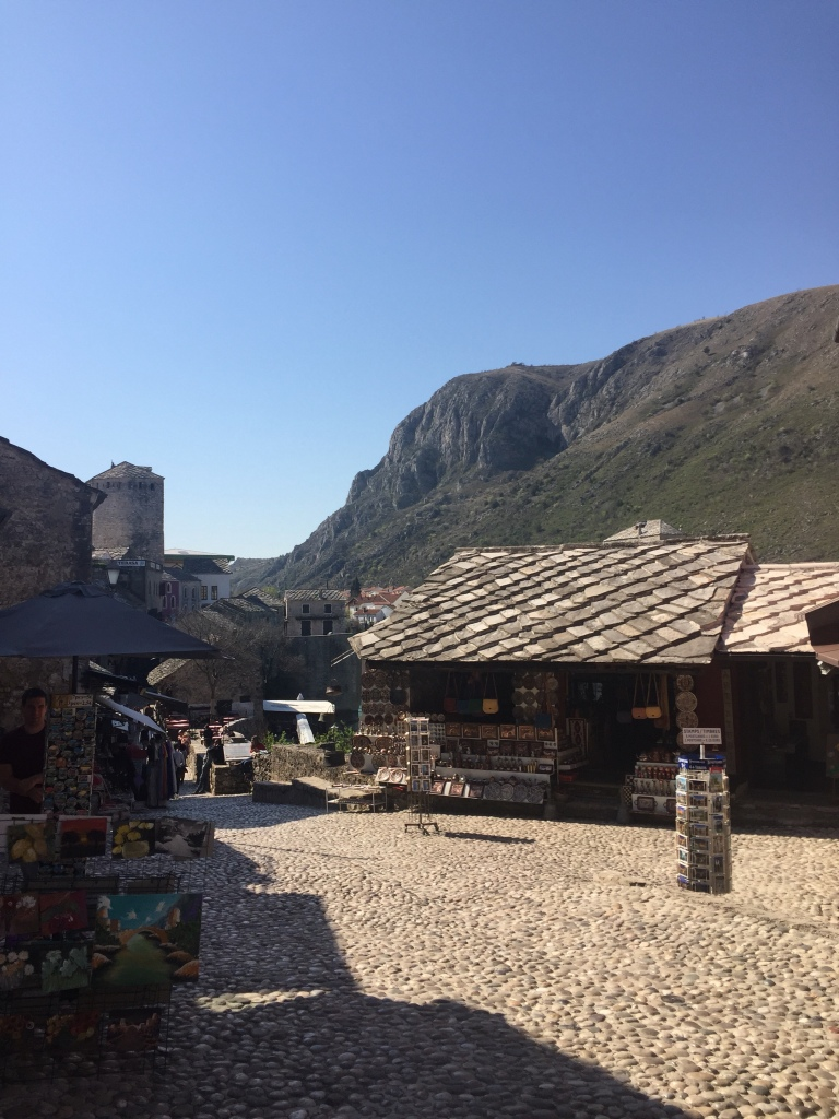 The entrance to the old market with cobbled flooring, stalls and the mountains in the backgroun