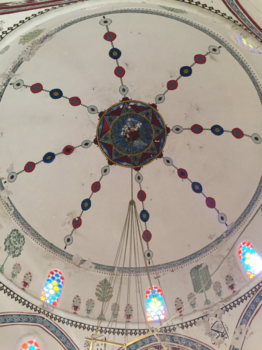 the ceiling of a mosque. There is a star like pattern in the centre. From each point you can see lines of bead like shapes are coming from it towards the edges of the ceiling. Small windows below this reveal brightly coloured light from the sun through the stain-glass windows
