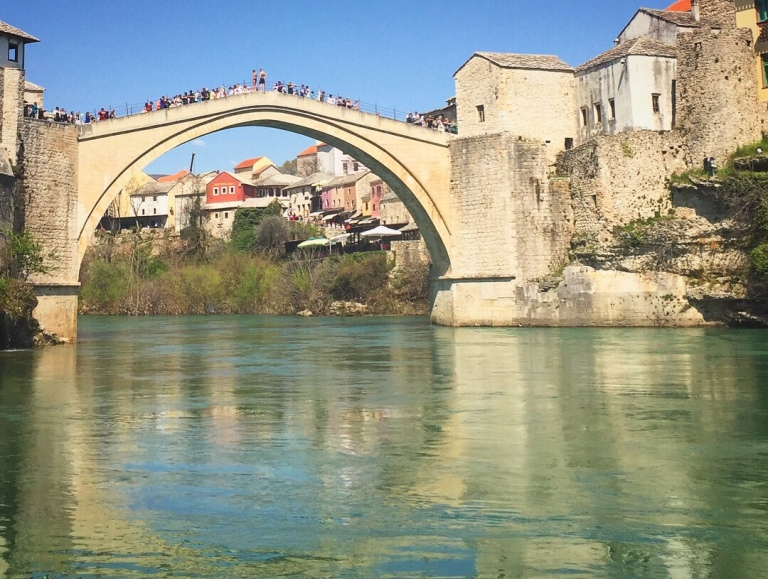 The old bridge is over the incredibly clear waters that reflect the bridge like a mirror in Bosnia and Hertz. Mostar