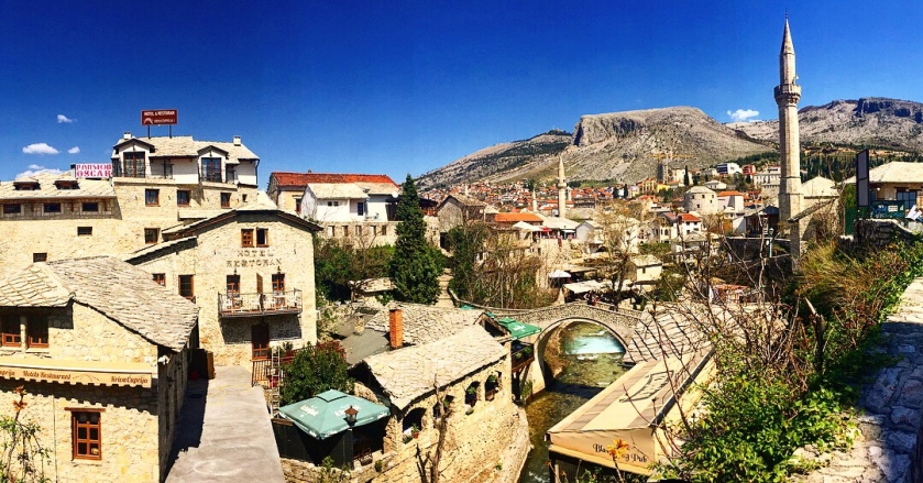 The old town in Bosnia and Hertz. in Mostar you can see the mountain in the background with old buildings and a mosque in the foreground.