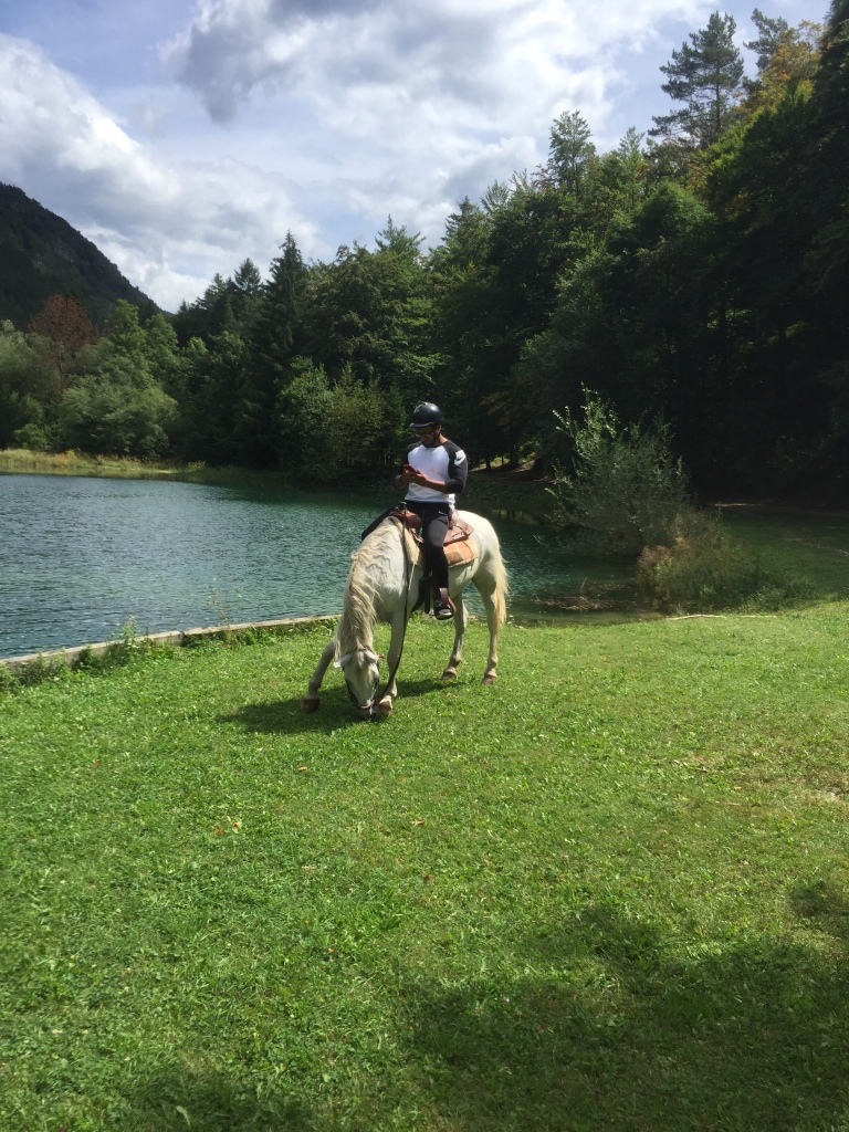 Taking a break from horse riding to let the horse, Tim, eat some fresh green grass by the pond / lake in Bled, Slovenia.