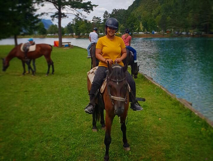 Charlie the brown horse in Bled Slovenia being ridden in a yellow top