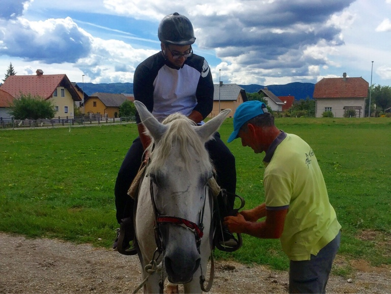 Ifran in a helpment getting ready to ride the horse called Tim around the mountains in Bled Slovenia