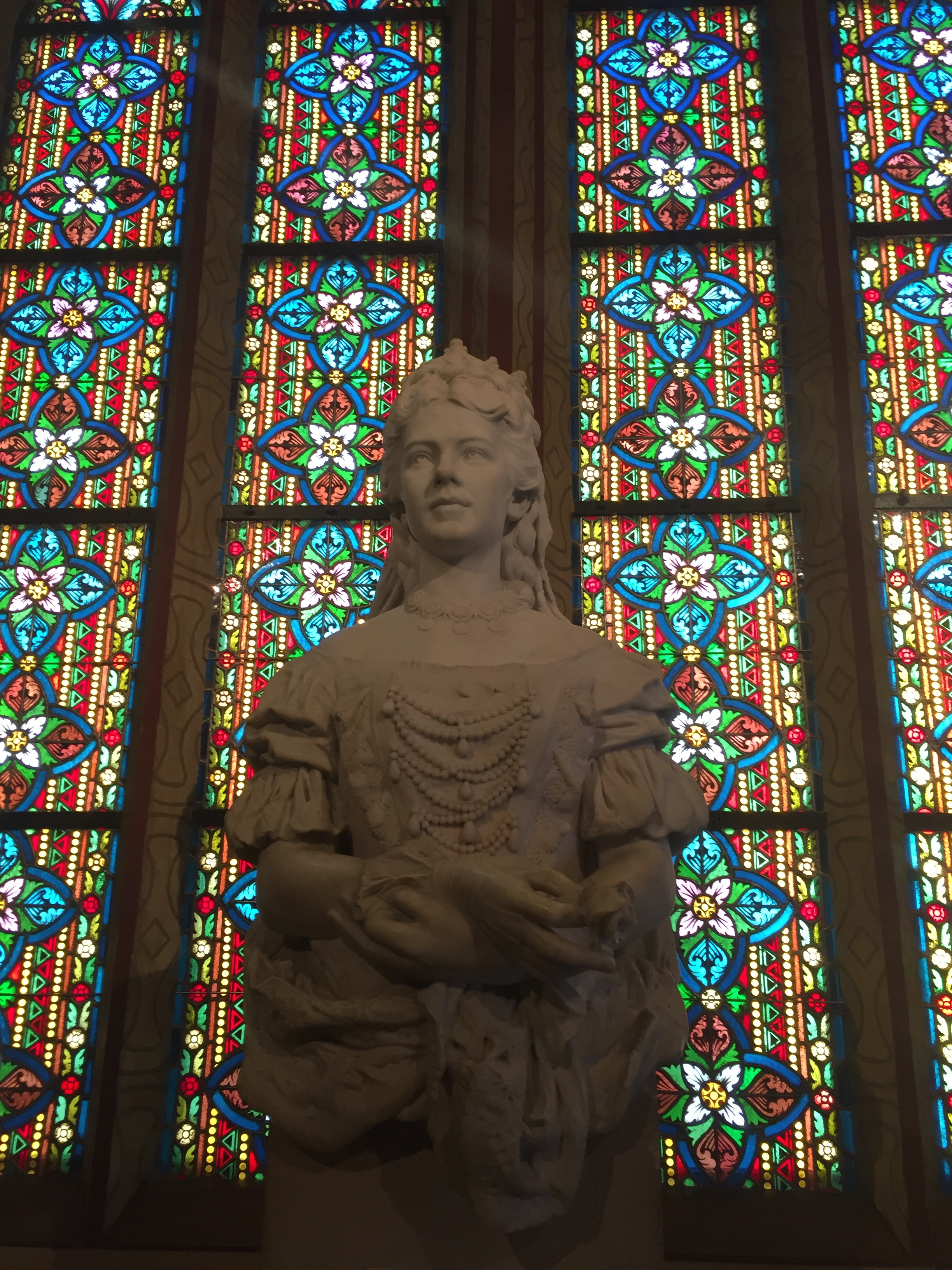 Statue of The late Queen Elisabeth of Hungary in front of stain glass windows