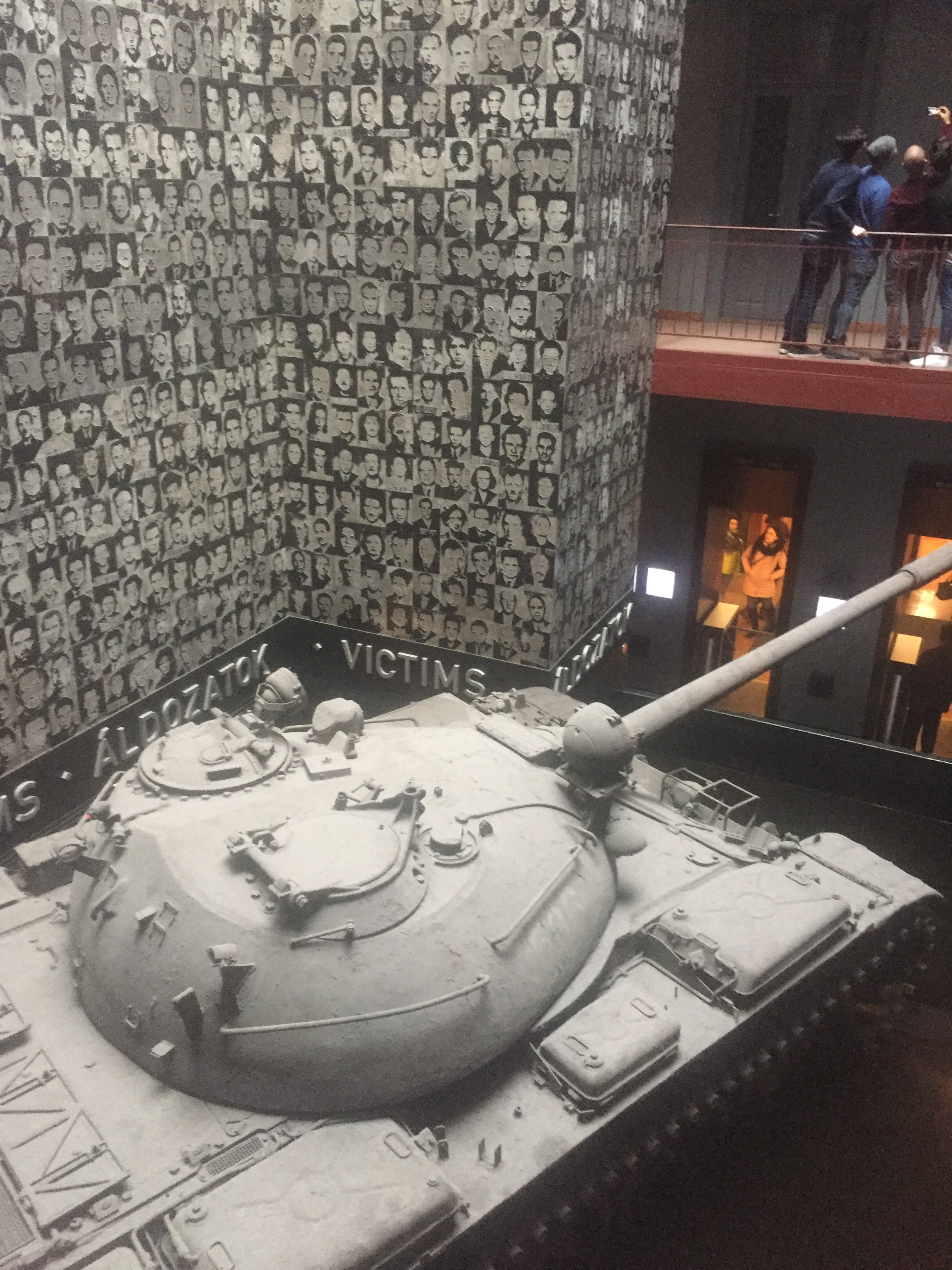 Inside the house of terror in Budapest is a tank and a wall of victims faces.