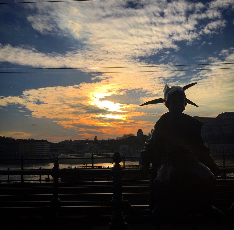 Sunset in Budapest from the promenade with a statue sat on the fence.