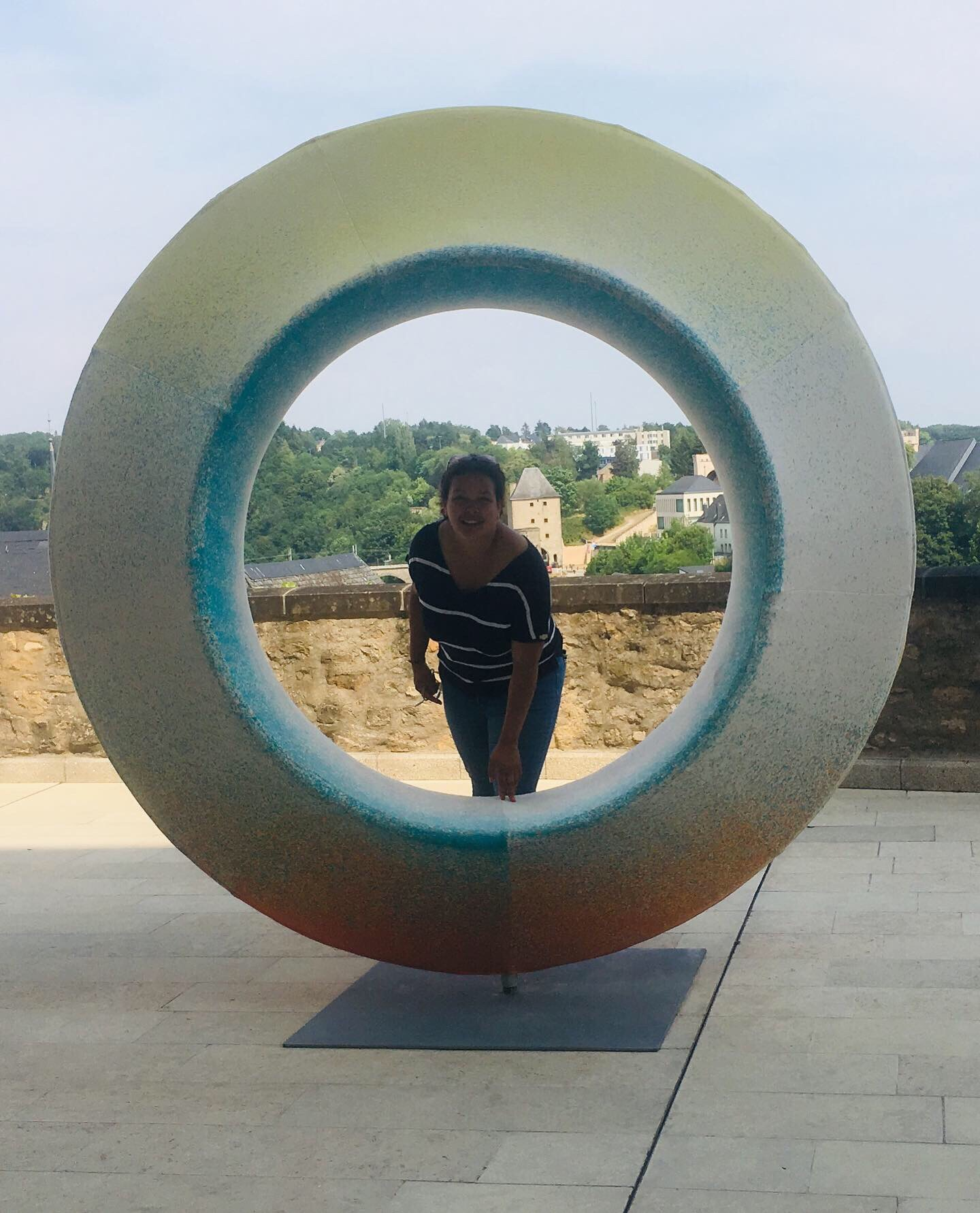 A girl stands inside of a blue arty circle