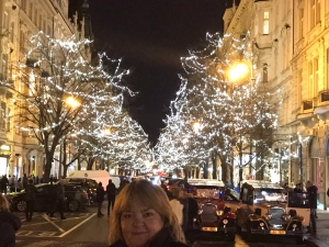 My mum travelling in Prague in front of Christmas tree lights